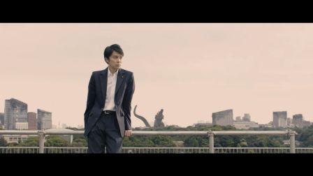 Una delle scene finali di Godzilla. In primo piano si vede il protagonista. Dietro di lui, tra i palazzi di Tokyo, svetta la sagoma del Godzilla ibernato.